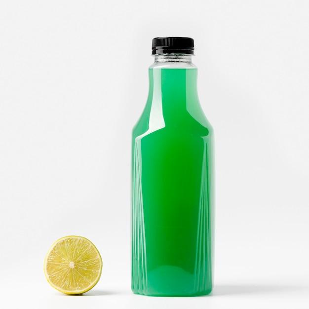 Vista frontal da garrafa de suco verde com limão Foto gratuita