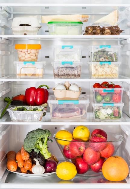 Vista frontal da geladeira aberta com caçarolas e legumes Foto gratuita