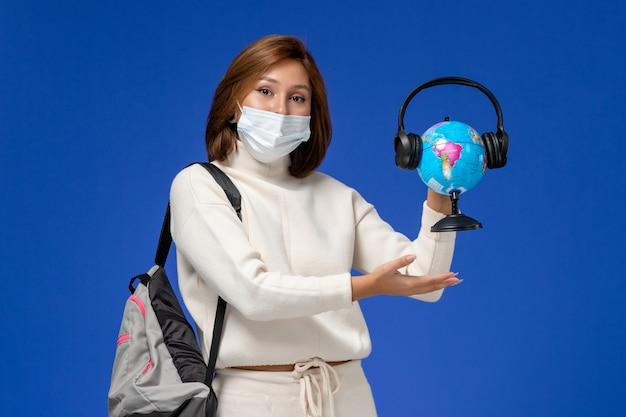 Vista frontal da jovem aluna em camisa branca usando máscara e mochila segurando o globo com fones de ouvido na parede azul Foto gratuita