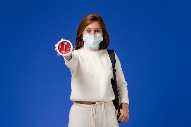 Vista frontal da jovem aluna em camisa branca, usando máscara e segurando o relógio na parede azul Foto gratuita