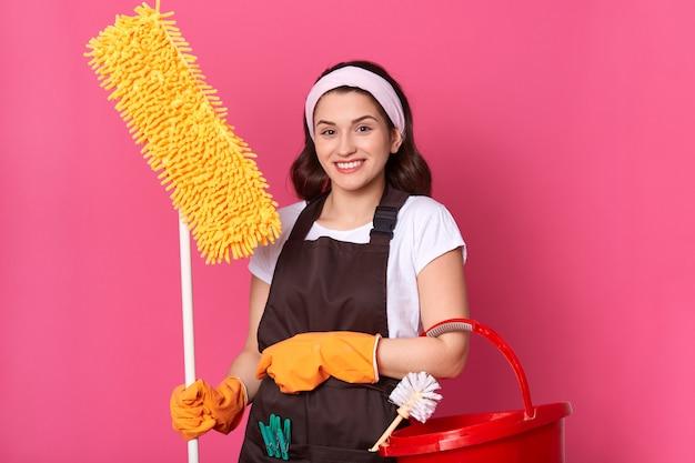 Vista frontal da jovem dona de casa sorridente com roupas casuais e avental Foto gratuita