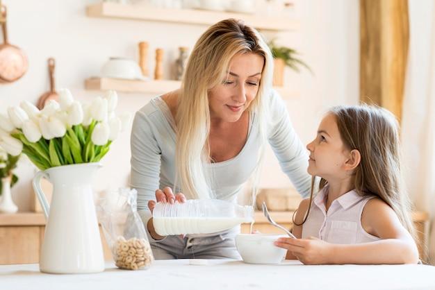 Vista frontal da mãe derramando leite sobre os cereais da filha Foto gratuita