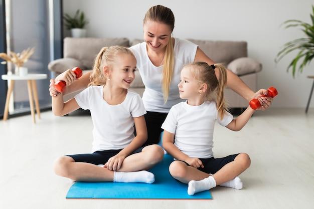 Vista frontal da mãe e filhas exercitando em casa Foto gratuita