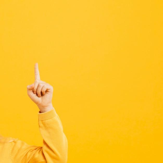 Vista frontal da mão apontando para cima com espaço de cópia Foto gratuita