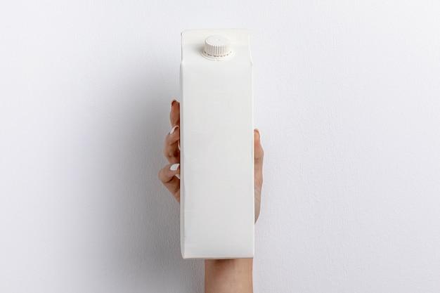Vista frontal da mão segurando a caixa de leite simples Foto gratuita