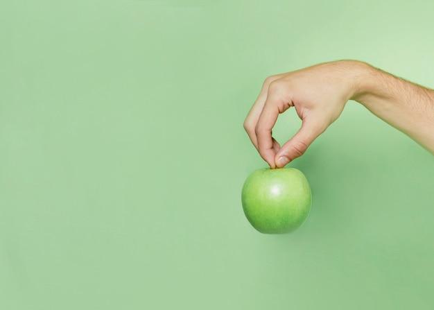 Vista frontal da mão segurando a maçã Foto gratuita