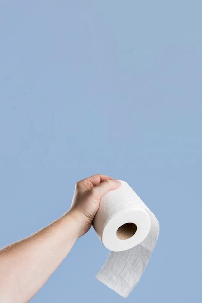 Vista frontal da mão segurando o papel higiênico com espaço de cópia Foto gratuita