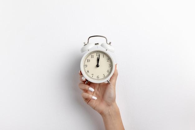 Vista frontal da mão segurando o relógio com espaço de cópia Foto Premium