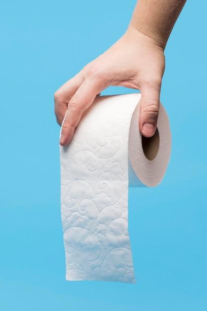Vista frontal da mão segurando o rolo de papel higiênico branco Foto Premium