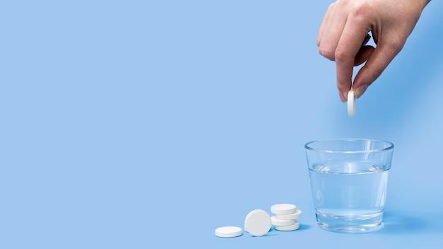 Vista frontal da mão soltando comprimido efervescente em copo de água com espaço de cópia Foto Premium