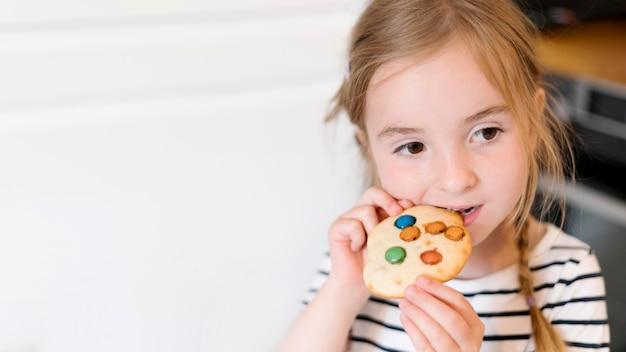 Vista frontal da menina comendo um biscoito Foto gratuita