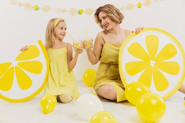 Vista frontal da menina e mulher brindando com limonada Foto gratuita