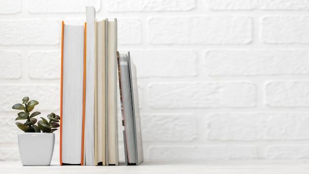 Vista frontal da mesa com livros empilhados e espaço de cópia Foto gratuita