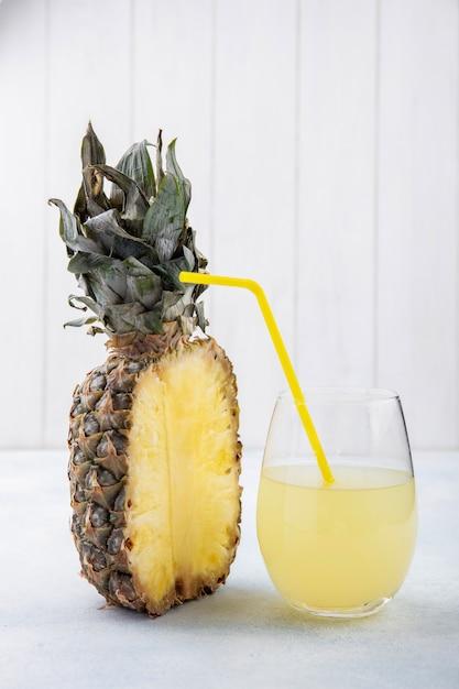 Vista frontal da metade do abacaxi e copo de suco de abacaxi com tubo na superfície branca Foto gratuita