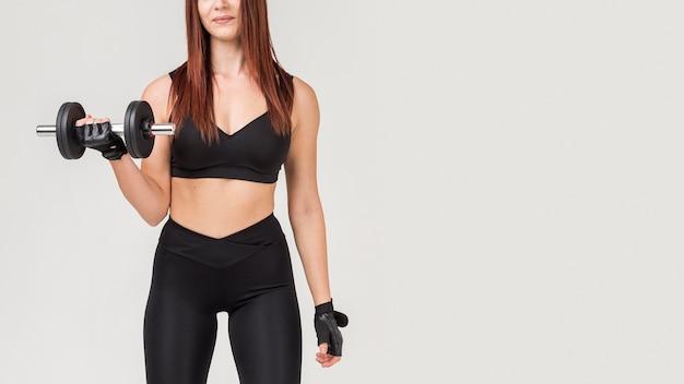 Vista frontal da mulher atlética, exercitar-se com peso Foto gratuita