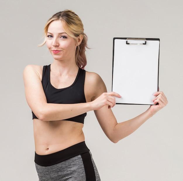 Vista frontal da mulher atlética, sorrindo e segurando o bloco de notas Foto gratuita