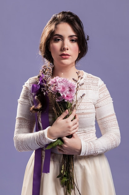 Vista frontal da mulher bonita posando com buquê de flores Foto gratuita