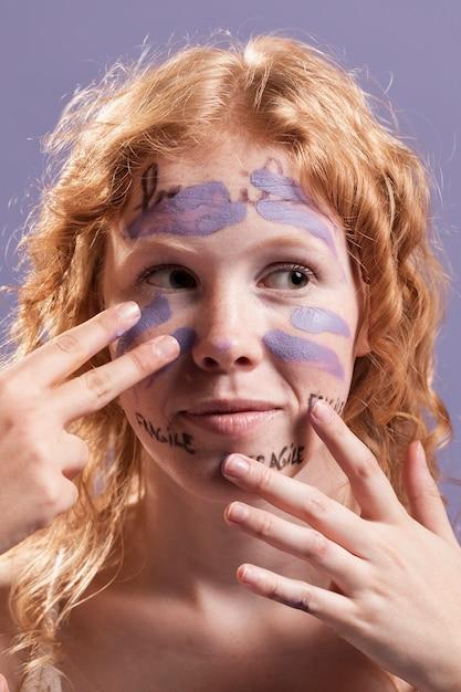 Vista frontal da mulher cobrindo palavras com tinta Foto gratuita