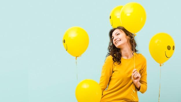 Vista frontal da mulher com balões Foto Premium