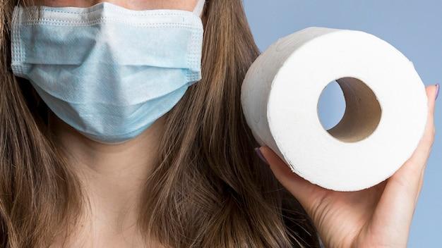 Vista frontal da mulher com máscara médica segurando papel higiênico Foto gratuita