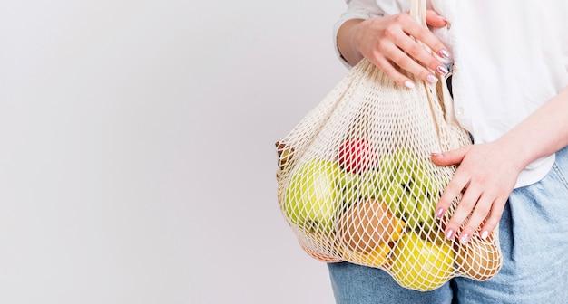Vista frontal da mulher com saco de frutas Foto gratuita