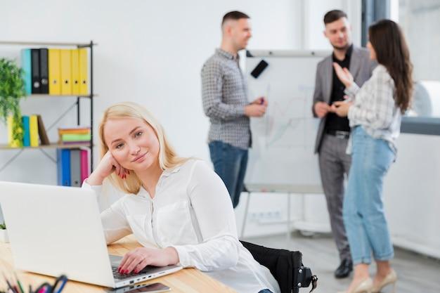 Vista frontal da mulher em cadeira de rodas, posando no trabalho enquanto colegas conversam Foto gratuita