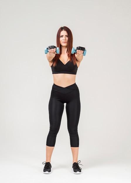 Vista frontal da mulher em exercício exercitar com pesos Foto gratuita