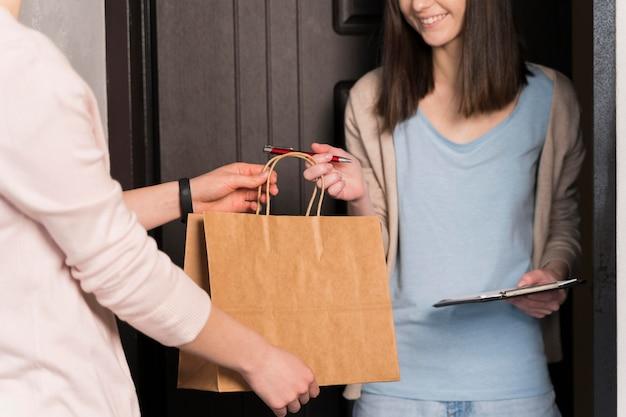 Vista frontal da mulher entregando entrega, mantendo o bloco de notas e caneta Foto Premium