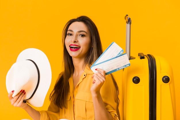 Vista frontal da mulher excitada segurando bilhetes de avião Foto gratuita