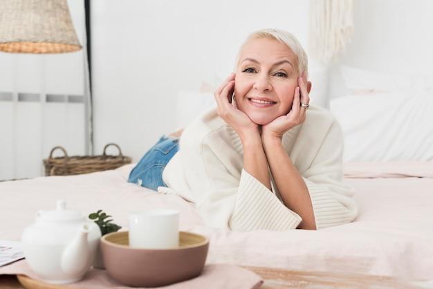 Vista frontal da mulher feliz madura, sorrindo e posando na cama Foto gratuita