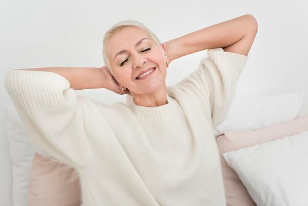 Vista frontal da mulher idosa sorridente alongamento Foto gratuita