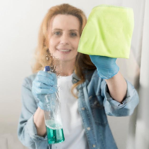 Vista frontal da mulher limpando a janela Foto gratuita