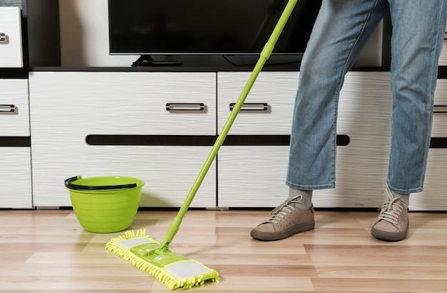 Vista frontal da mulher limpando o chão Foto gratuita