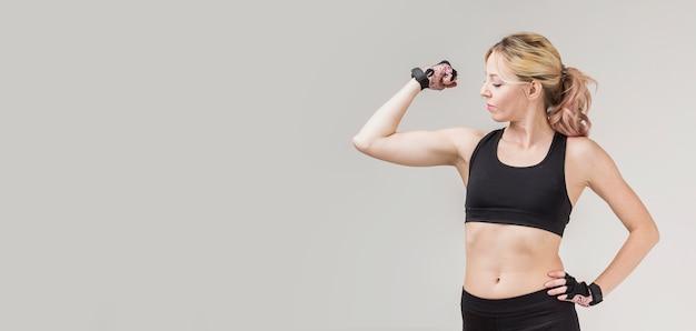 Vista frontal da mulher mostrando seu bíceps com espaço de cópia Foto gratuita