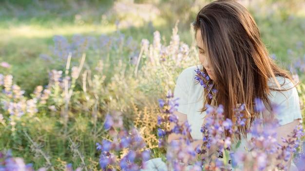 Vista frontal da mulher na natureza admirando flores Foto gratuita
