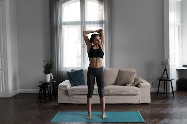 Vista frontal da mulher no sportswear, estendendo-se no tapete de ioga Foto gratuita