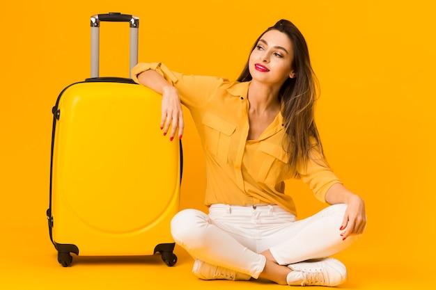 Vista frontal da mulher posando alegremente ao lado de sua bagagem Foto gratuita