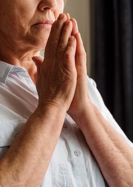 Vista frontal da mulher rezando Foto gratuita