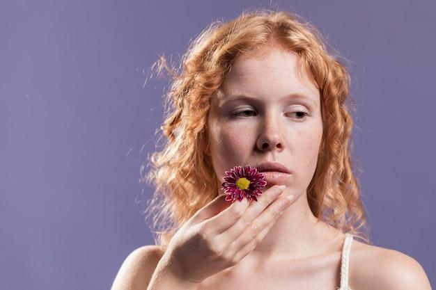 Vista frontal da mulher ruiva segurando uma flor perto da boca com espaço de cópia Foto gratuita