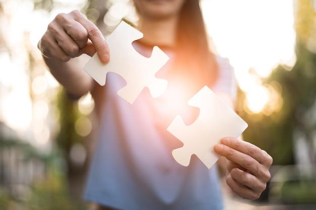 Vista frontal da mulher segurando as peças do puzzle Foto gratuita