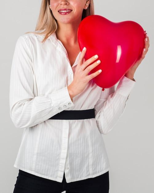 Vista frontal da mulher segurando balão de coração Foto gratuita