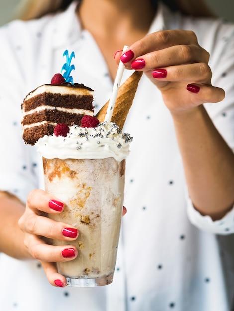 Vista frontal da mulher segurando delicioso milkshake Foto gratuita
