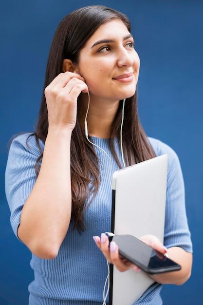 Vista frontal da mulher segurando laptop e ouvir música em fones de ouvido Foto gratuita