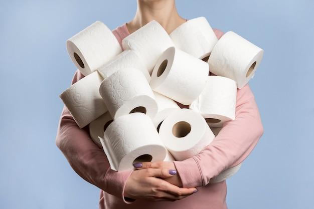 Vista frontal da mulher segurando muitos rolos de papel higiênico Foto Premium