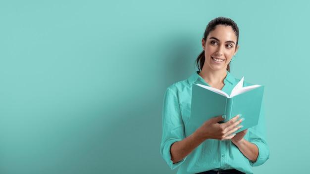 Vista frontal da mulher segurando o livro com espaço de cópia Foto gratuita
