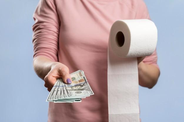 Vista frontal da mulher segurando o rolo de papel higiênico e oferecendo dinheiro Foto gratuita