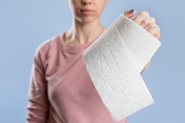 Vista frontal da mulher segurando o rolo de papel higiênico Foto gratuita