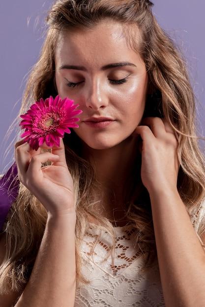 Vista frontal da mulher segurando um crisântemo perto do seu rosto Foto gratuita
