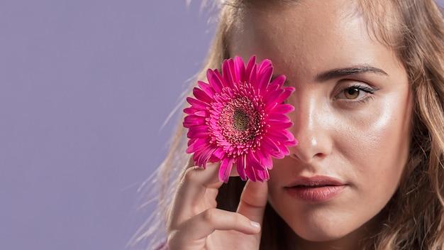 Vista frontal da mulher segurando uma flor perto do rosto com espaço de cópia Foto gratuita