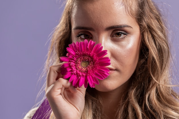 Vista frontal da mulher segurando uma flor perto do rosto Foto gratuita